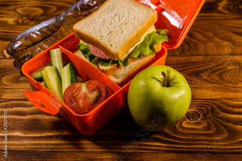 Foto op Aluminium Assortiment Bottle of water, green apple and lunch box with sandwich, cucumbers and tomatoes on wooden table