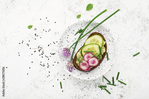 Canvas Print Toast avocado puree, cucumber, onion, onion flowers, radish and daikon on slices of dark bread on a light background with sesame seeds