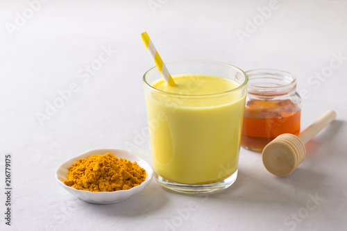 Golden milk with turmeric in a glass on a gray stone background. healthy natural energy drink. selective focus