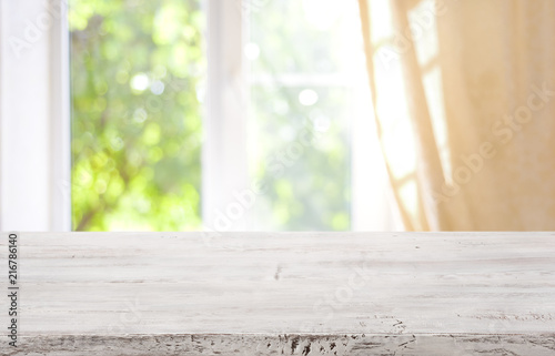 Pinturas sobre lienzo  Wooden table top on blurred window background for product display