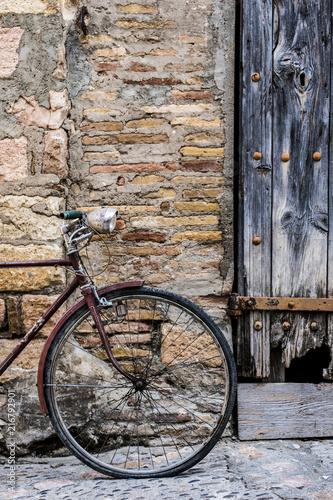 stary-rower-doladowany-na-rustykalnym-scianie-w-wiosce-ulicy-sredniowiecznego-pochodzenia-w-miejscowosci-alquezar-w-prowincji-huesca-w-aragon-w-hiszpanii-w-europie