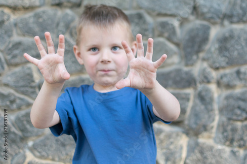 A small boy of 3-5 years fools around and spread his fingers on a stone background.