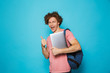 canvas print picture - Photo of caucasian youngster guy with curly hair wearing casual clothing and backpack holding laptop, isolated over blue background