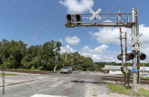 Summerfield, Florida, USA, 2018. Railroad signals and track passing through North Florida countryside. Car crossing the junction.