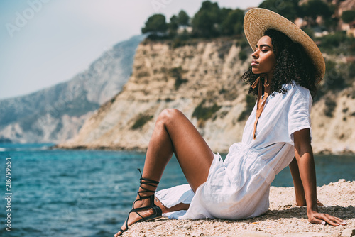Woman with straw hat relaxing on beach