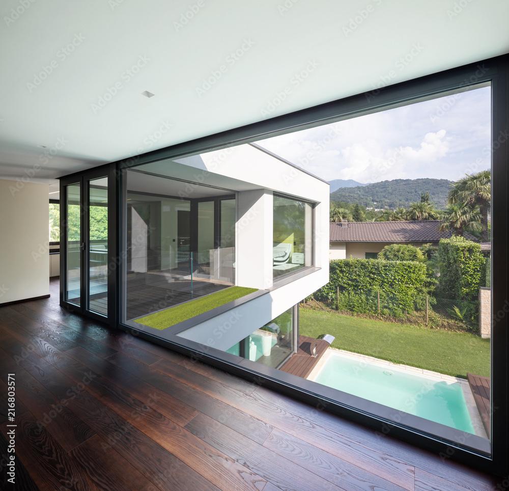 Fototapeta Large window in hallway of modern villa overlooking the private pool