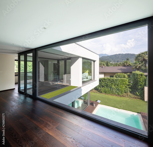 Fototapeta Large window in hallway of modern villa overlooking the private pool obraz