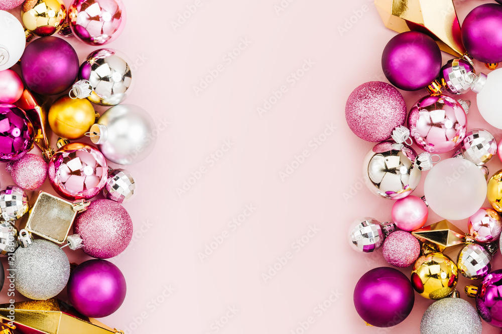 Fototapeta Holiday  arrangement with Stylish Christmas shiny baubles and gold crystals on pastel pink background. Flat lay, top view