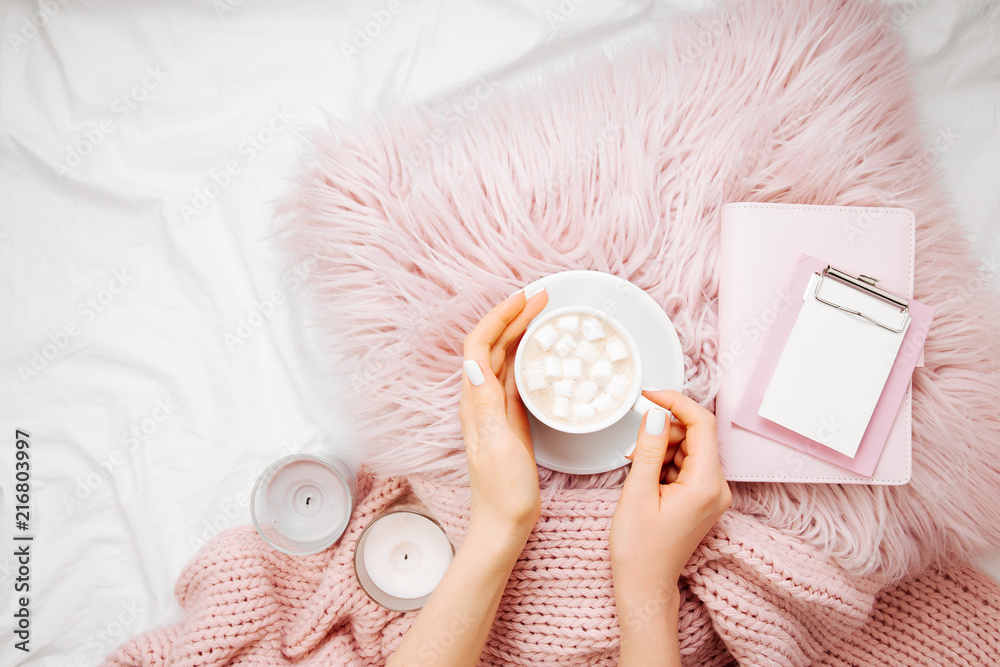 Fototapety, obrazy: A cup of coffee on a pink pillow with notebook and a blanket on the bed. Flat lay, top view