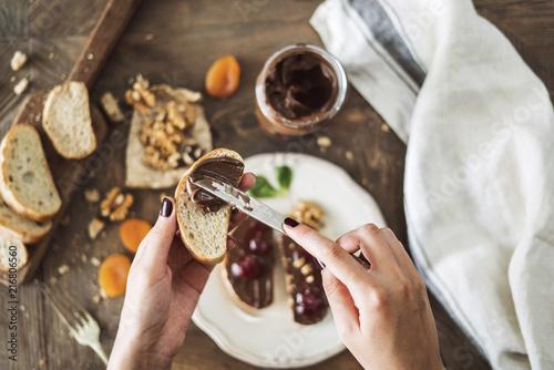 Carta da parati Woman spreading chocolate cream on slice bread
