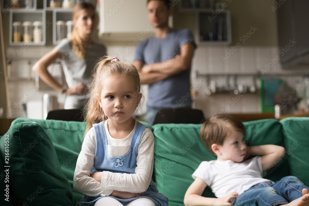Fototapety, obrazy: Frustrated kid girl feels upset, offended or bored ignoring avoiding worried parents and brother, little sad sister not talking to child boy after fight sulking sitting on couch, siblings rivalry