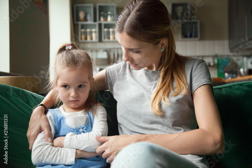 Obraz Loving mother consoling or trying make peace with insulted upset stubborn kid daughter avoiding talk, sad sulky resentful girl pouting ignoring caring mom embracing showing support to offended child - fototapety do salonu
