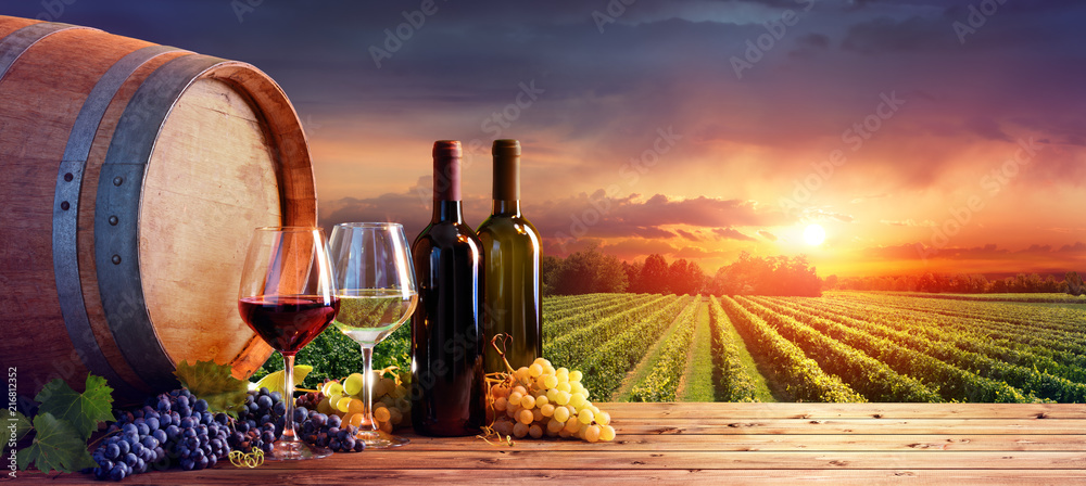 Fototapeta Bottles And Wineglasses With Grapes And Barrel In Rural Scene