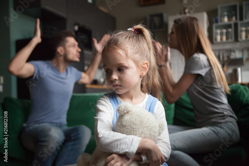Kid daughter feels upset while parents fighting at background, sad little girl frustrated with psychological problem caused by mom and dad arguing, family conflicts or divorce impact on child concept