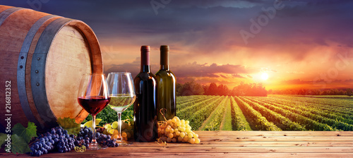 Photo Stands Wine Bottles And Wineglasses With Grapes And Barrel In Rural Scene