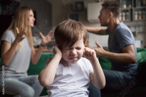 Valokuva Frustrated kid son puts fingers in ears not listening to noisy parents arguing,