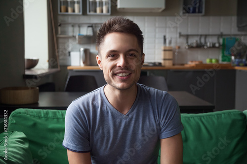 Fotografía  Smiling young man looking at camera sitting on sofa in the kitchen, millennial g