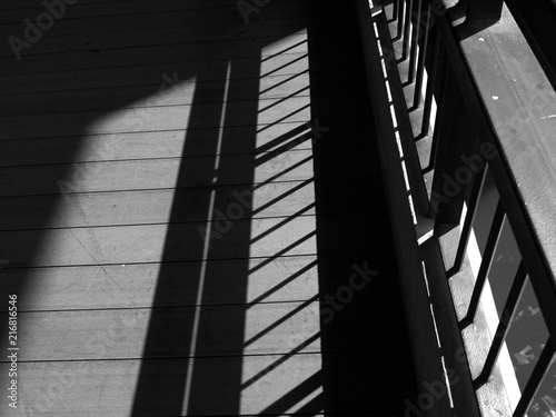 Fotografie, Obraz  A closeup of view of a jail cells iron bars casting shadows on the prison floor