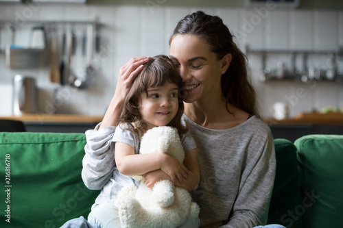 Fotografia  Happy single mother hugging cute daughter showing care support, young smiling mo