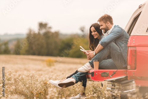 Fotografía  side view of happy young couple using gadgets while sitting in car trunk during