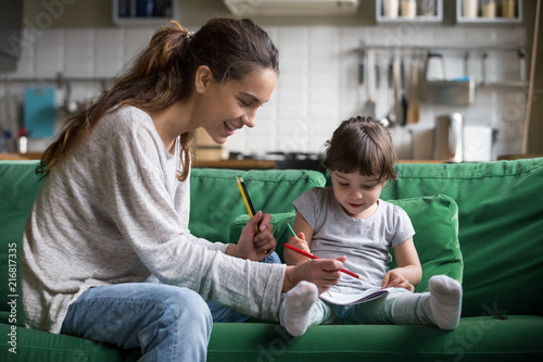 Fotomural Smiling baby sitter and preschool kid girl drawing with colored pencils sitting
