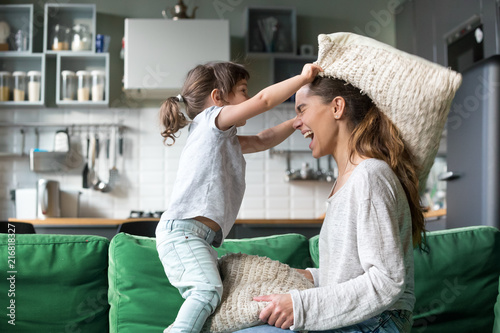 Photo Mommy and kid daughter having pillow fight together, young babysitter nanny play