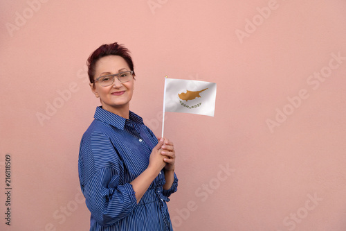 Staande foto Cyprus Cyprus flag. Woman holding Cypriot flag. Nice portrait of middle aged lady 40 50 years old with a national flag over pink wall background.