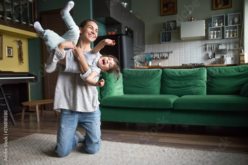 Excited mother holding lifting kid daughter flying laughing on weekend, young family single mom or babysitter nanny playing with active cute girl at home, happy mommy and child having fun together