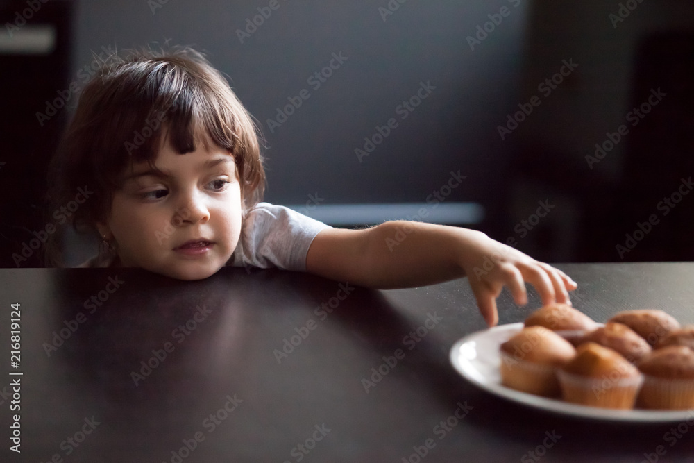 Fototapeta Cunning cute little girl stealing delicious muffin on table, hungry funny impatient child reaching hand to take homemade cookies from plate, unhealthy food and kids sugar craving addiction concept