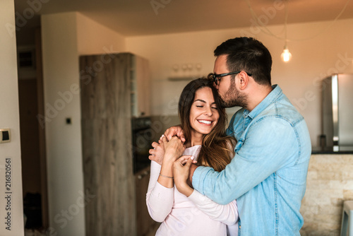 Young man kissing his wife in the forehead indoors. Wallpaper Mural