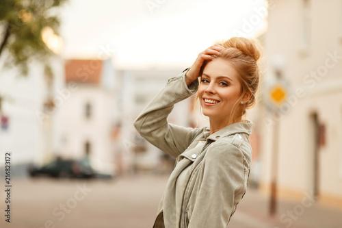 Fototapeta premium Stylowa piękna młoda kobieta uśmiechając się w modnej jesiennej kurtce w mieście