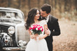 canvas print picture - Just married happy couple in the retro car on their wedding