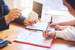 Couple hands are signing mortgage loan agreement.Contract agreement policy concept.