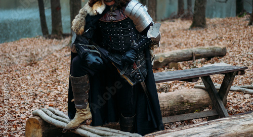 Photo  Medieval knight with sword in armor as style Game of Thrones in the forest