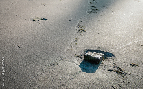 Valokuva  Stone in a dimple on the beach