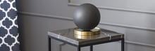 Real Photo Of A Decorative Boule Standing On A Table In Living Room Interior With Molding On A Wall