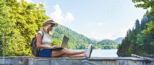 Beautiful girl traveler in a hat on a lake with a laptop Work outside the office Fotobehang