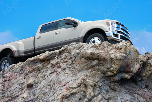 Photo Big rugged pickup truck driving on the edge of a rocky cliff ledge with a bright blue sky in the background