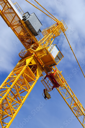 Orange construction tower crane with jib and hook isolated on blue sky with whit Fototapeta