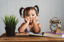 Cute Little Asian Baby Toddler Making Boring Face While Reading Books With Alarm Clock. Child Growth, Early Education And Learning Concept