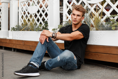 Fototapeta Stylish handsome young man in black T-shirt with jeans and shoes sitting on the beach obraz na płótnie