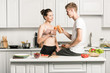 young couple clinking with bottles of healthy juice in kitchen
