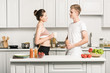 side view of young couple holding cups and looking at each other in kitchen