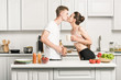 side view of young couple holding cups and kissing in kitchen