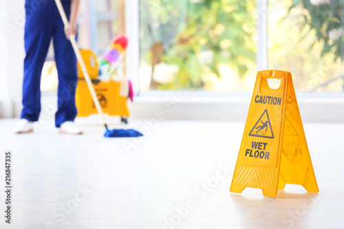 Fotografia, Obraz Safety sign with phrase Caution wet floor and blurred cleaner on background