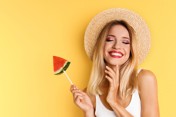 Pretty young woman with juicy watermelon on color background