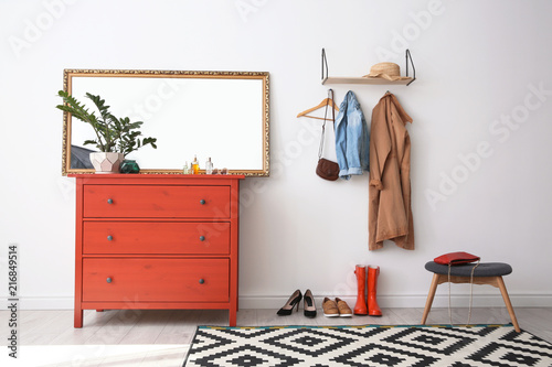 Stylish hallway interior with mirror and chest of drawers
