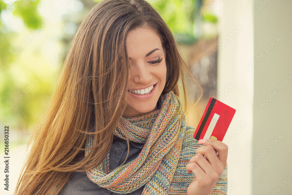 Fototapeta Cheerful excited young woman with credit card standing outdoors