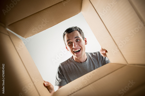 Photo The surprised man unpacking, opening carton box and looking inside