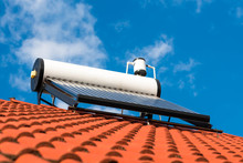 Solar Water Heater With Boiler On Roof Top, Blue Sky With White Clouds Background.